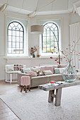 Living room in pale shades with arched windows and high ceiling
