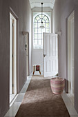 Brown runner in hallway with high ceiling and arched window