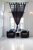 Two black leather armchairs in room with high ceiling and dark curtains on windows