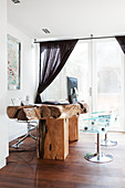 Transparent shell chairs at rustic desk made from live-edge wood
