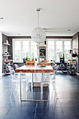 Transparent designer chairs around dining table in masculine kitchen-dining room