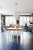 Transparente Designerstühle um den Esstisch in maskuliner Wohnküche