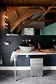 Washstand in rustic bathroom with black wall and wood-beamed ceiling