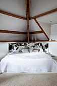 Bed with piebald cowhide headboard below sloping ceiling with exposed wooden beams