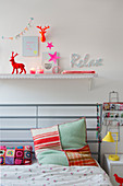 Colourful accessories on shelf above bed with handmade cushions