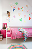 Colourful love-harts on wall above bed with lacy pink blanket in girl's bedrm