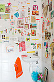 Colourful gallery of items stuck on wall with washi tape above sink