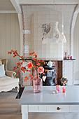 Dahlien und orange blühender Zweig im Wohnzimmer mit Kachelofen