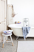 Stool in front of the free-standing bathtub and a privacy screen with worn paint