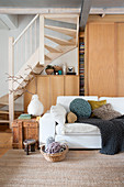 White sofa and rustic wooden crate used as side table in front of fitted cupboards below wooden staircase