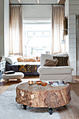 Rustic coffee table made from chunky section of tree trunk, white easy chair and couch in living room