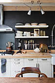 White kitchen counter with wooden worksurface against black wall