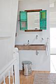 Türkises Dekofenster mit Spiegel überm Waschbecken aus Stein