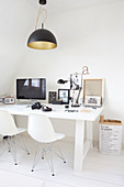 Black-and-white utensils on white desk and white classic chairs