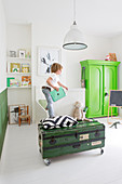 Boy stood on bed in white bedroom with green vintage furniture