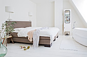 Double bed and ensuite bathroom in white