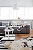 Pale grey sofa and standard lamp in front of window and side table on black-and-white striped rug