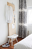 White blouse hung on wooden panel, stool and black-and-white curtain in bedroom