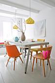 Metalltisch mit verschiedenen Stühlen in Pastelltönen
