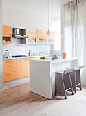 Yellow kitchen counter, white island counter and bar stool in open-plan kitchen