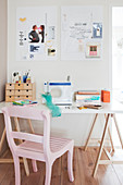 Work area: sewing machine on white table and pink wooden chair