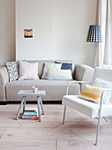 Scatter cushions on pale grey sofa, armchair and stool used as small table in living room