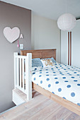 Blue polka-dot bed linen on wooden bed below pendant lamp with paper lampshade