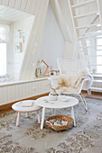 Rattan armchair and placemat in a white room with a dormer window