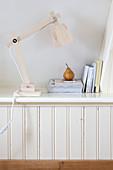 Leselampe, Bücher und eine Birne auf Ablage in Dachschräge