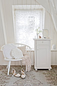 White cupboard and chair with pillows in front of the window in the attic room