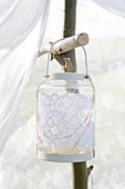Lantern decorated with white lace hangs on the garden pavilion made of branches and a curtain