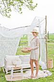Sofa im DIY-Gartenpavillon aus Ästen und weißem Vorhang, im Vordergrund Frau mit Körbchen