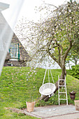 White hanging chair on the tree in the garden