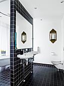 Waschbecken und Spiegel an Trennwand mit schwarzen Fliesen