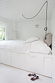White bed with drawers underneath in a white bedroom