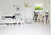 White couch with side tables and dining area with various chairs in a white, open living room