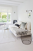 White couch with pillows, side tables and metal basket in a white living room