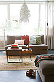 Scatter cushions on sofa and retro coffee table in front of window in living room