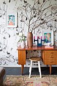 Retro desk and stool against bird-patterned wallpaper