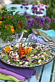 Salad with French marigold petals and bouquet of parsley on garden table
