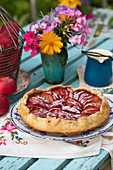 Homemade apple pie and vase of flowers on garden table