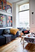 Gerahmte Plakate überm Sofa im winterlichen Wohnzimmer