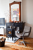 Retro swivel chair in front of a small stove in the fireplace