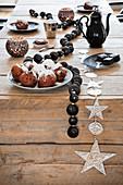 Winterliche Deko mit schwarzer Perlenkette auf rustikalem Holztisch