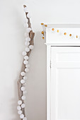 Christmas decorations on white cupboard next to cotton ball fairy lights on branch