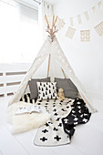 Black-and-white cushions and blanket in wigwam with fairy lights