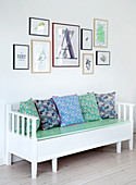 Extendable Swedish bench with flowered cushions under picture gallery