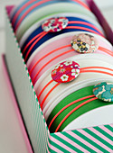 Rubber bands with fabric buttons around rollers with fabric straps