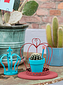 Blau bemalter Pflanztopf mit Kaktus unter roter Deko-Krone
