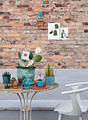 Rusty metal table with cacti and vintage decorations in front of a brick wall